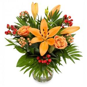 En vacker blombukett i varma, oranga toner. Liljor, rosor m m.