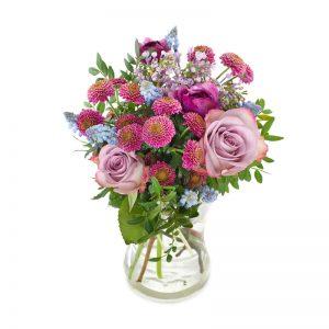 Bukett med blandade vårblommor i rosa, lila och blått tillsammans med grönt. Från Euroflorist.