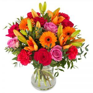 Bukett med blandade blommor i rött, rosa och orange. HÄr; rosor, liljor och gerberas. Mycket färgstark och stilig bukett från Euroflorist.
