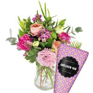 Bukett med blommor i rosa och aprikos plus en strut choklad. Från Gift2day.