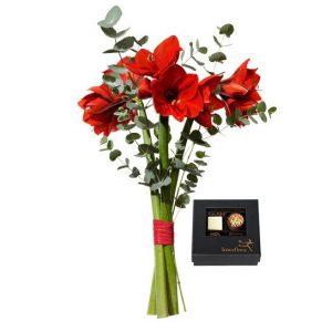 Interfloras decemberbukett, med röda amaryllis och eucalyptus +en ask med chokladpraliner (4 st). Överraska med ett blomsterbud från Interflora till jul!