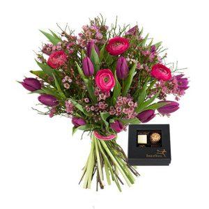 Bukett med blommor i cerise/lila;  ranunkel, tulpaner, vaxblomma och blåbärsris. Plus en ask praliner. En produkt ur Interfloras sortiment.