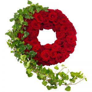 Elegant begravningskrans med mängder av röda rosor, ackompagnerade av murgröna på ena sidan. Beställ begravningskransen online hos Euroflorist, så skickas den med bud ända till aktuell kyrka eller kapell.
