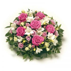 Rund blomsterkudde med rosor, fresia och grönt. Skicka den med ett bud från Euroflorist direkt till aktuell begravning - beställ enkelt online.