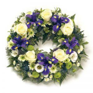 Begravningskrans med rosor, iris, krysantemum och säsongsgrönt. BLommorna går i vitt och lila. Beställa kransen online hos Euroflorist och låt dem buda ut den direkt till platsen för begravningen.