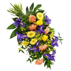 Sorgbukett med nejlikor, iris, rosor, germini och säsongsgrönt. Blommorna går i gult, rosa och lila. Begravningsbuketten ingår i Euroflorists utbud av begravningsblommor.