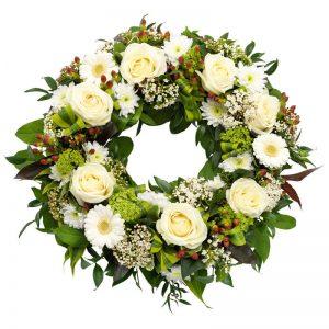 Klassisk begravningskrans med rosor, gerbera, krysantemum, snöbollsbuske, hypericum och gröna blad. Beställ kransen online hos Euroflorist, för leverans direkt till aktuell begravning.