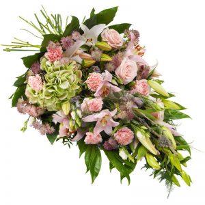 Begravningsbukett med blommor i rosa; lilja, nejlika, rosor, prärieklocka, astrantia och säsongsgrönt. Finns hos Euroflorist.