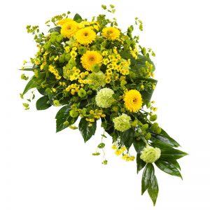 Begravningsdekoration med germini, santini, nejlika och gröna blad. Den ingår i Euroflorists utbud av begravningsdekorationer.