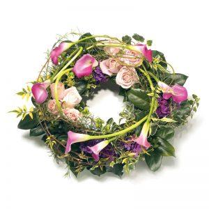 Begravningskrans ur Euroflorists sortiment av begravningsblommor; med kallor, rosor, hortensia och gröna blad.