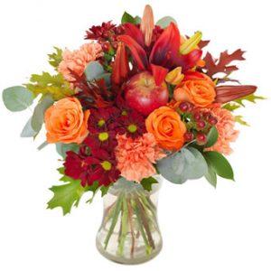 Blombukett med rosor, nejlikor, liljor och krysantemum i orange o rött tillsammans med gröna blad. En superfin Halloweenbukett från Euroflorist.