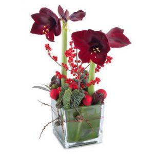 Glasvas med röda amaryllis. Röda bär och julpynt i basen som dekoration. Supertjusig! Juldekorationen finns att beställa som blomsterbud i Euroflorists e-butik.