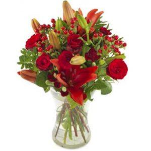 Julbukett med röda rosor och blandade blommor i rött tillsammans med grönt. Julgruppen ingår i Euroflorists sortiment av julblommor.