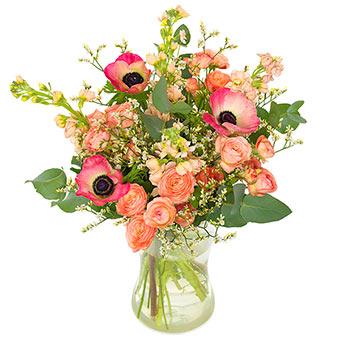 Bukett med blandade rosa blommor tillsammans med grönt. Blommorna ingår i Euroflorists bukettsortiment.