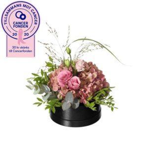 Liten rund blomsterdekoration i rund ask, med hortensia, prärieklocka, eukalyptus och gröna blad. Blomsterdekorationen finns att beställa online i Interfloras egen e-butik