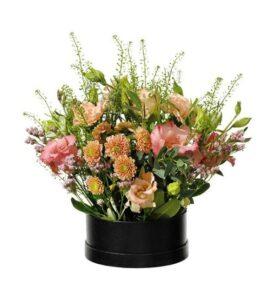 Rund ask med blomsterarrangemang med nejlikor, prärieklockor och santini. Finns hos Interflora